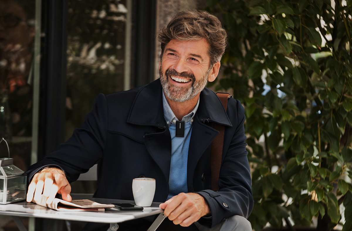 man at table with Oticon Opn hearing aids and ConnectClip_1200x788