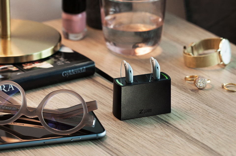 Oticon Opn hearing aids in rechargeable battery charger on desk